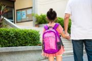 Elementary- Parent holding student hand going into school.