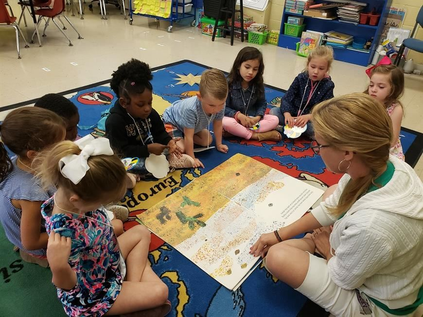 Image of Kindergarten teacher showing students a book on the carpet