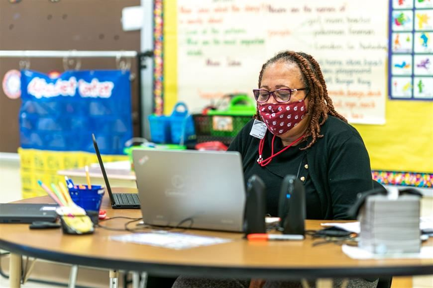 CCS teacher working on her computer at a desk