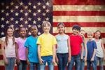 group of smiling students in front of an American Flag