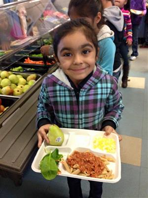 little girl smiling, wearing plaid jacket holding her lunch tray