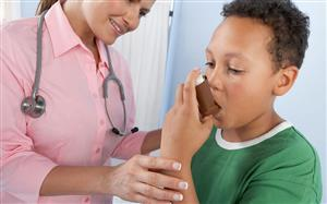 School nurse wearing pink administering a inhaler to a child, brown with curly hair