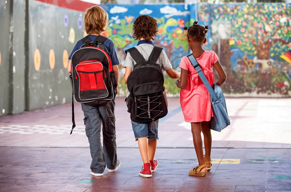 Three children wearing bookbags, walking away while holding hands.