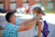 Parent putting mask on child returning to school