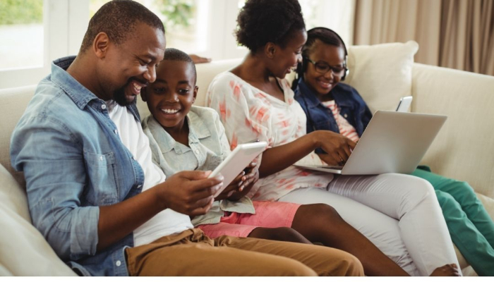 Family sitting on the couch using mobile devices